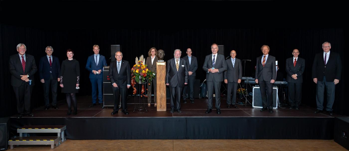 Der Preisträger (Mitte) mit Festgästen